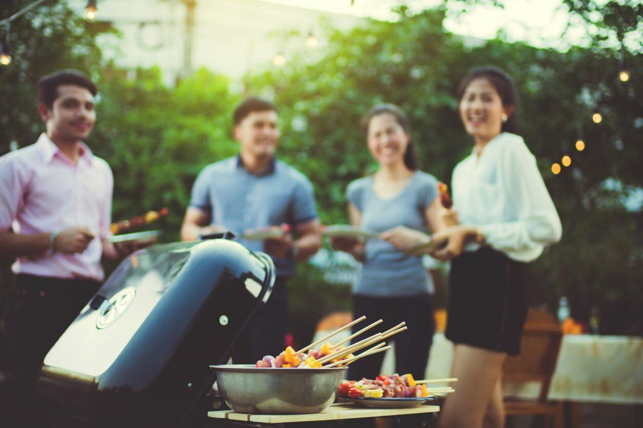 Friends gather around a BBQ